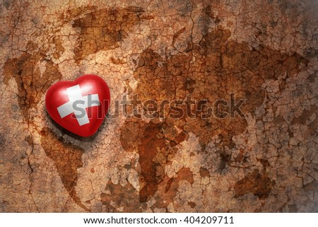 heart with national flag of switzerland on a vintage world map crack paper background. concept - stock photo