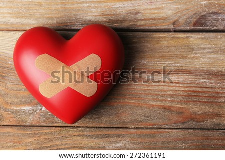 Heart with plaster on wooden planks background - stock photo