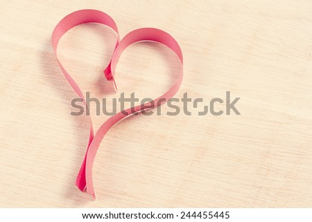Heart with red ribbon over wooden background