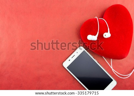 Heart with smartphone and earphones closeup on red with copy-space - stock photo