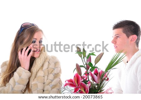 Heartbroken young man offering Valentines bouquet of flowers to a girl that ignores him - stock photo
