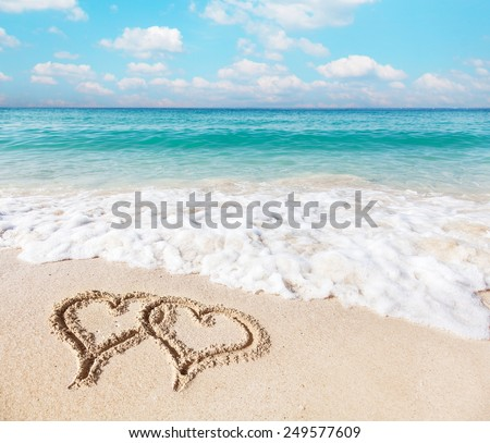 Hearts drawn on the beach sand. - stock photo