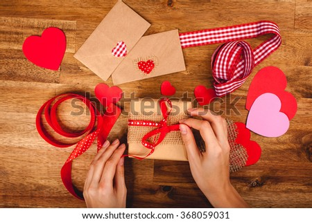 Hearts, gift, ribbons, envepopes on wood background. Woman's hands making handmade valentines day decoration - stock photo