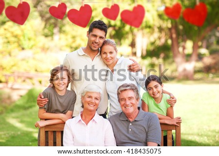 Hearts hanging on a line against family in the park - stock photo