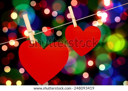 Hearts hanging on a line against light glowing dots design pattern