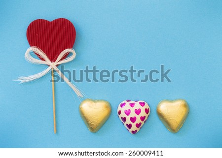 hearts in gold packaging and blue background - stock photo