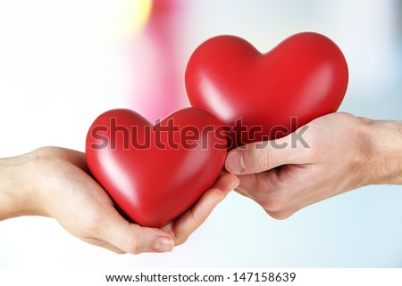 Hearts in hands on light background