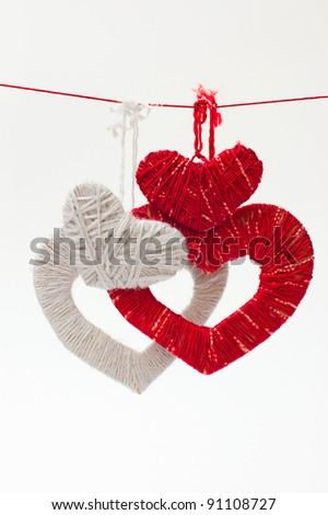 Hearts made of red and grey threads is hangings on a rope - stock photo