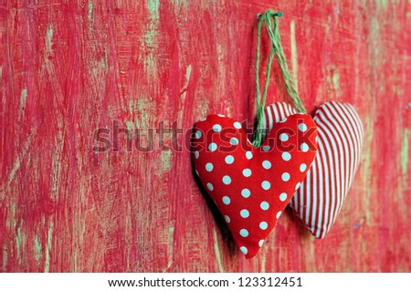 Hearts on red painted background - stock photo