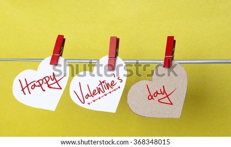 hearts with clothespins hanging on clothesline on color background. date, love Happy Valentines Day concept - stock photo