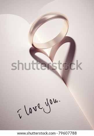 heartshadow with rings on a book middle - i love you - card - stock photo