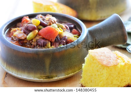 Hearty bowl of chuckwagon chili con carne with beef, beans, corn, tomato and cornbread - stock photo