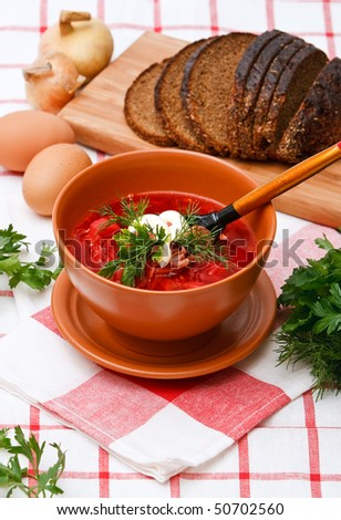 Hearty bowl of homemade red borsch with sour cream and parsley - stock photo