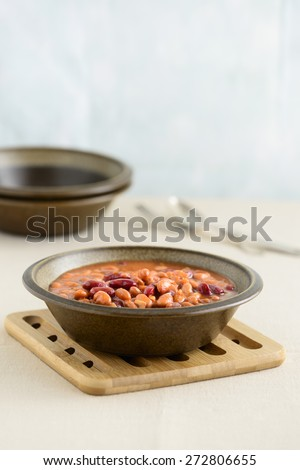 Hearty bowl of mixed beans in a sauce. - stock photo