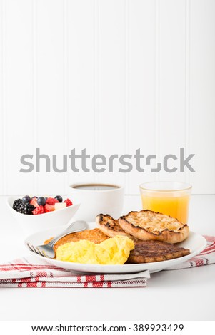 Hearty breakfast of scrambled eggs and sausage with coffee and orange juice. - stock photo