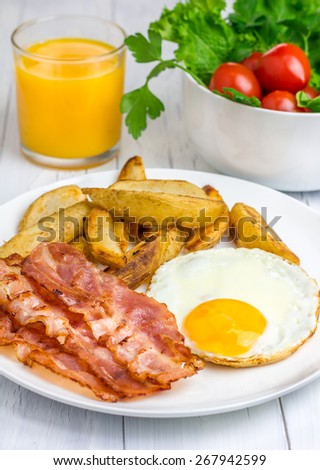Hearty breakfast with bacon, fried egg, potato and glass of orange juice - stock photo