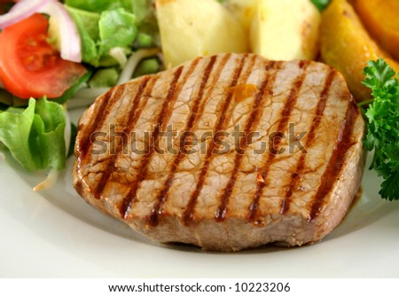 Hearty dinner of grilled steak, vegetables and a side salad.