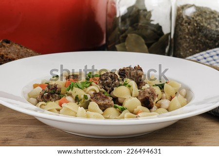 Hearty dinner of Italian sausage, white bean and shell pasta soup with homemade rye toast - stock photo