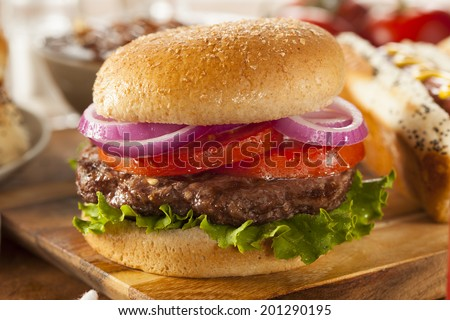 Hearty Grilled Hamburger with Lettuce and Tomato on a Bun - stock photo