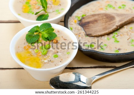Hearty Middle Eastern Chickpea and Barley Soup with mint leaves on top - stock photo