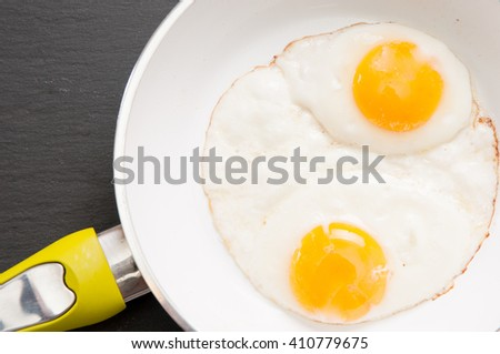 hearty omega threee free range large fried eggs in a skillet - stock photo