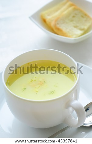 heat bouillon in white bowl and three pieces of bread - stock photo