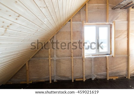Heat insulation and wooden logs lathing ready for Finishing made of tongue and groove planks. An interior view of unfinished home inside - stock photo