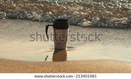 Heat protection-thermos coffee cup on the beach, close to the waves and nestled into the center of grainy sand - stock photo