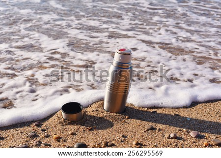 Heat protection-thermos coffee tea cup on the beach, close to the waves, nestled into the center of grainy sand, sandy beach, bank of sea ocean - stock photo