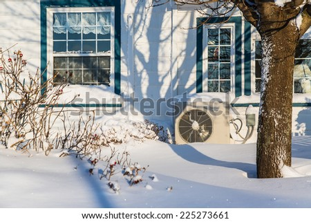 Heat pump unit on the side of a home in winter. - stock photo