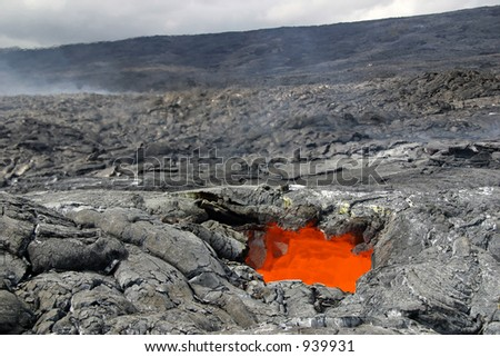 Heat rising from a glowing lava skylight (an opening in the roof of a lava tube) seen on a lava adventure hike - Hawaii Volcanoes National Park - stock photo