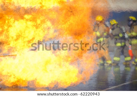 Heat waves partially obscure a team of firefighters. - stock photo