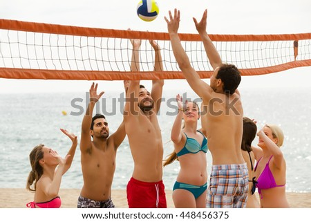 Heated adults happy friends playing volleyball at sandy beach - stock photo