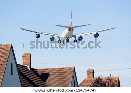 HEATHROW AIRPORT, LONDON - 9 SEPTEMBER: VIrgin Atlantic A340 approaches Heathrow on 9 September 2012.  London Heathrow is the world's third busiest airport and a new runway is under discussion. - stock photo