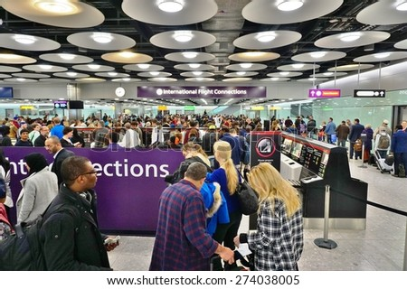 HEATHROW, ENGLAND -16 MARCH 2015- Passengers in transit wait in line at the busy International Flight Connections in the Terminal T5 at London Heathrow International Airport (LHR). - stock photo