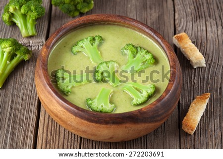 Heathy cream of broccoli green delicious soup with croutons in wooden bowl - stock photo