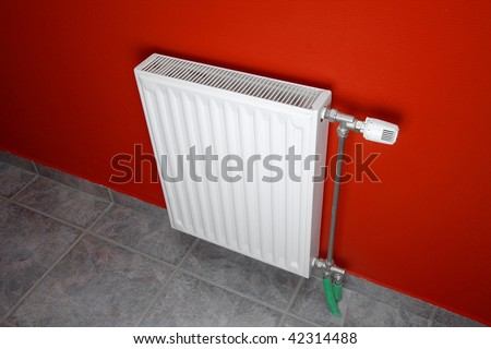 Heating radiator in a room with red wall - stock photo