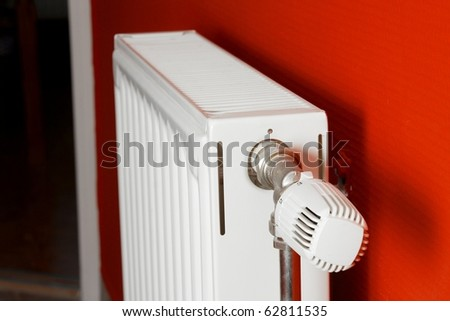 Heating radiator in a room with red wall, shallow focus - stock photo