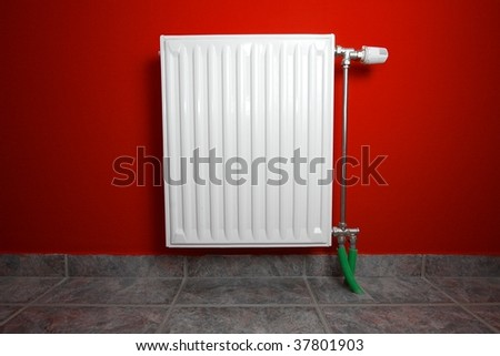 Heating radiator on red wall in a building interior - stock photo