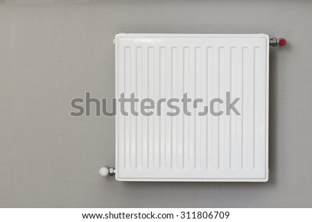 Heating radiator with thermostat. Connection is done through the wall - stock photo