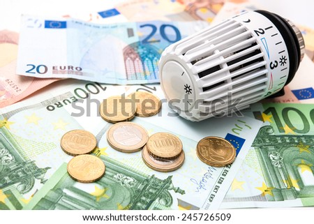 Heating thermostat with money, expensive heating costs concept - stock photo