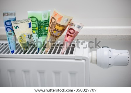 heating thermostat with money, expensive heating costs concept