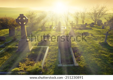 Heavenly light shining upon a old graveyard in England, United Kingdom.                                - stock photo
