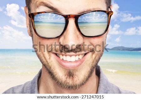 heavenly tropical destination reflected in young beautiful man's sunglasses. joyful portrait - stock photo