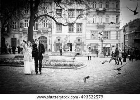 Heavenly wedding couple walks through the square while pigeons fly around them