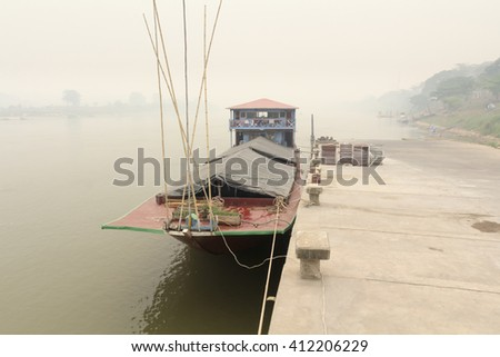 Heavily polluted air from forest fire smoke cover Mekong river at chiang khong port, Chiang rai ,Thailand. - stock photo