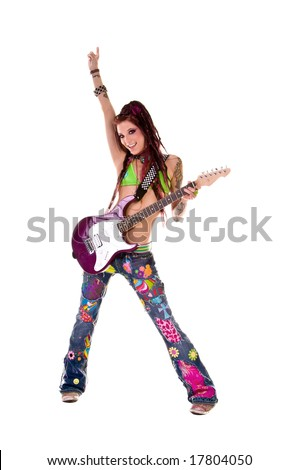 Heavily tattooed young hippie rocker woman in retro patchwork jeans and bikini top with long red dreadlocks playing electric guitar - stock photo