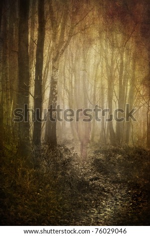heavily textured and toned abstract image of a ghostly figure wandering down a woodland path - stock photo