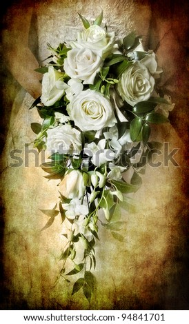 heavily textured and toned image of a bride holding a beautiful bouquet of white roses and orchids giving a vintage feel.