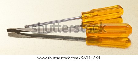 Heavily used slot and Philips screwdrivers on a galvanized sheet background